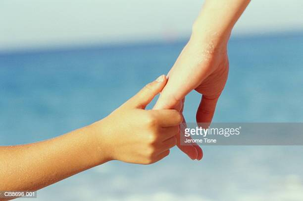 Child's hand holding woman's hand, sea in bckground, close-up