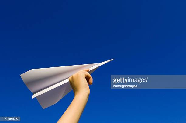 Child's hand lifting paper airplane on blue background