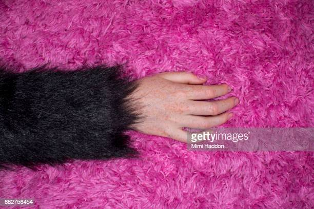child's hand on pink rug with fake fur sleeve - fur stock pictures, royalty-free photos & images