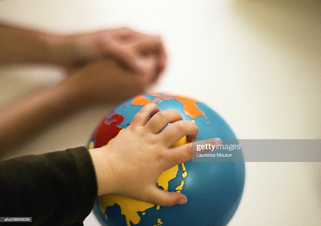 Childs hand on world globe. : Stockfoto