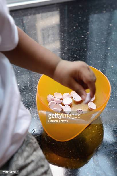 Child's hand picking yogurt snacks out of a bowl