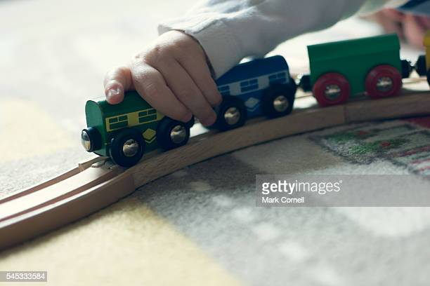 Child's hand playing with toy train