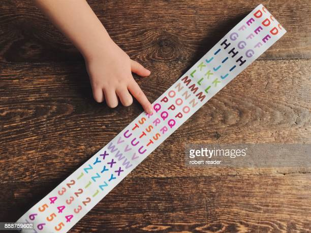 Child's hand pointing at colourful alphabet stickers