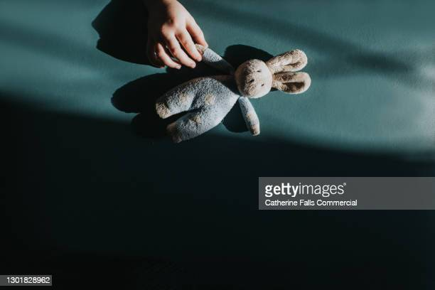 child's hand reaches for a small toy bunny - child stock pictures, royalty-free photos & images