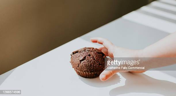 child's hand reaching for a chocolate chip bun - cake stock pictures, royalty-free photos & images
