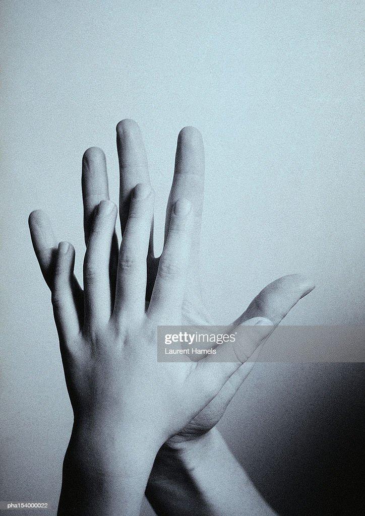 Child's hand touching man's hand, palm to palm, close-up, b&w. : Stockfoto