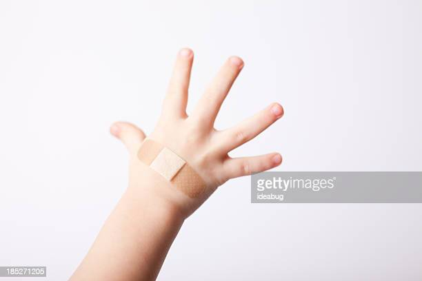 child's hand with bandage applied, isolated on white - cut on finger stock photos and pictures