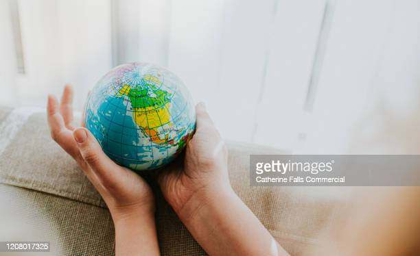 childs hands around a globe - climate change stock pictures, royalty-free photos & images