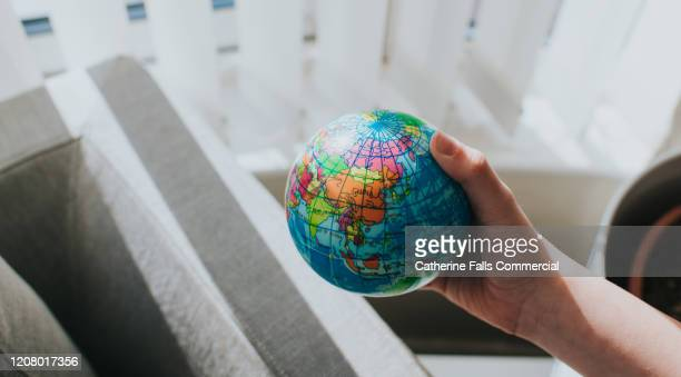 childs hands around a globe - organização das nações unidas - fotografias e filmes do acervo