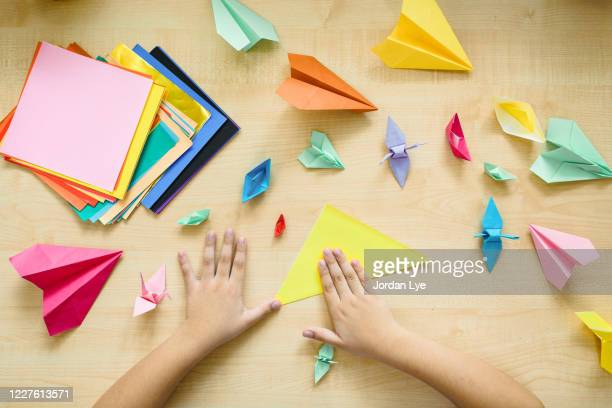 a child's hands folding origami at a table - learning disability stock pictures, royalty-free photos & images