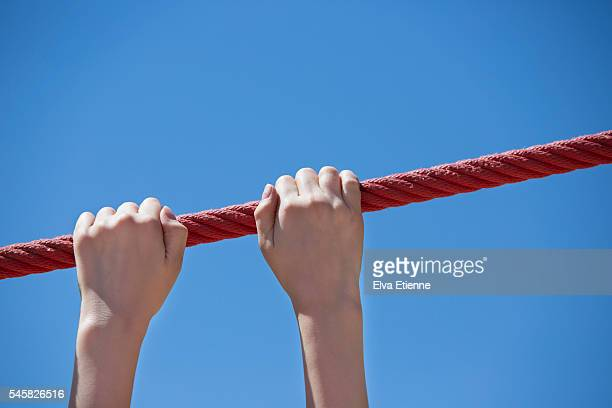 Child's hands gripping red rope