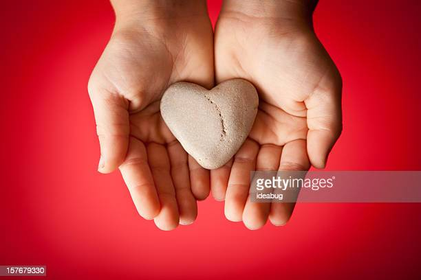 Child's Hands Holding a Heart-Shaped Rock on Red Background