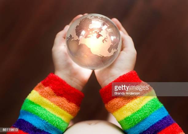 child's hands holding globe