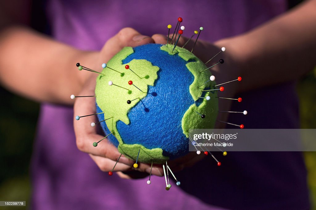 Childs hands holding hand made globe pin : Stock Photo