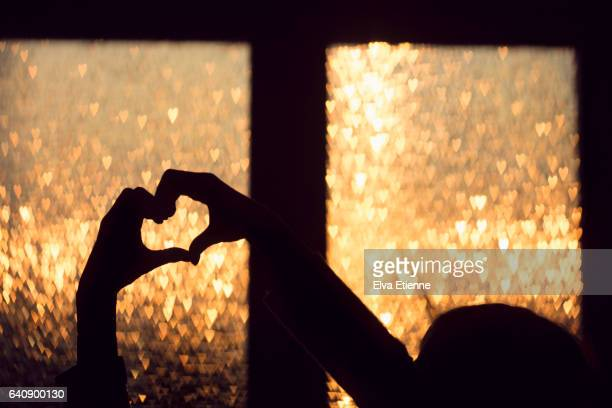 Child's hands making heart shaped silhouette against sunset through a window