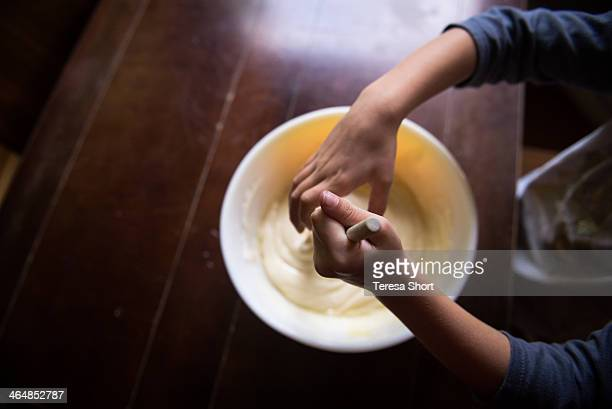 Child's hands mixing cake batter
