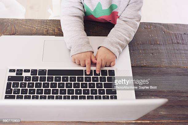 Childs hands on laptop computer keyboard