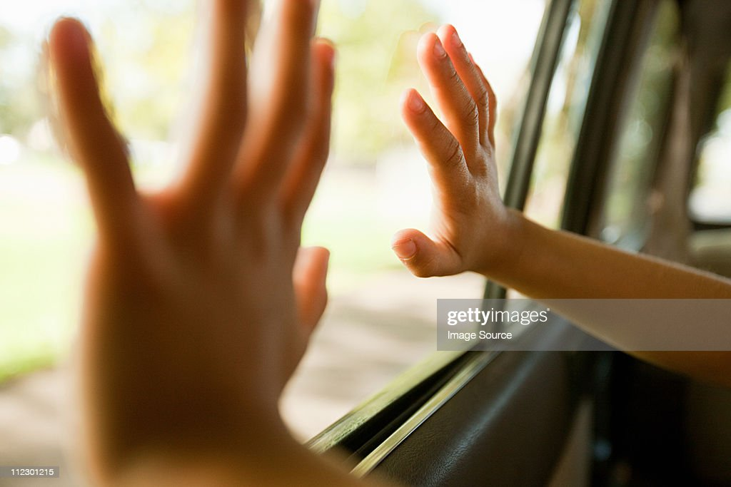Child's hands touching car window : Stock Photo