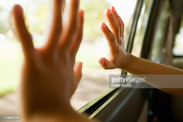 Child's hands touching car window