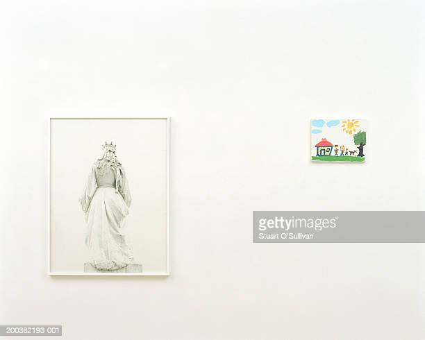 Child's painting mounted on wall next to picture in art gallery
