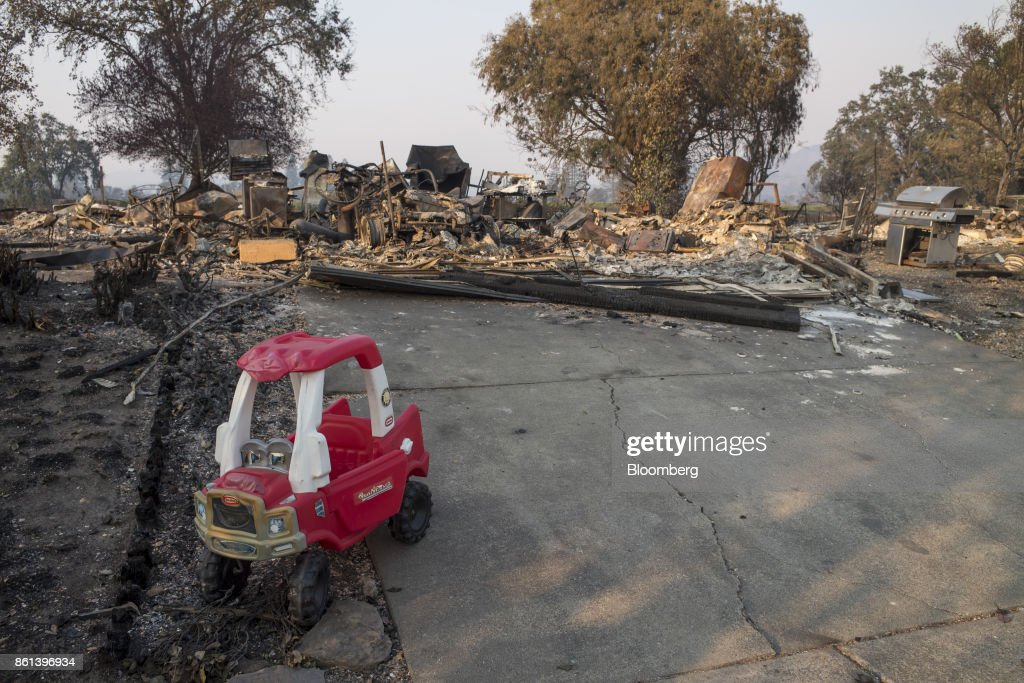 A child's play car sits in front of residences burned by wildfires in Santa Rosa, California, U.S., on Friday, Oct. 13, 2017. Wildfires that tore through northern California's iconic wine-growing regions have prompted evacuations of more than 20,000 people, killed 11 and damaged some of the most valuable vineyards and wineries in the U.S. About 1,500 commercial, residential and industrial structures were burned, and damage assessment teams have started accounting for the destruction. Photographer: David Paul Morris/Bloomberg via Getty Images