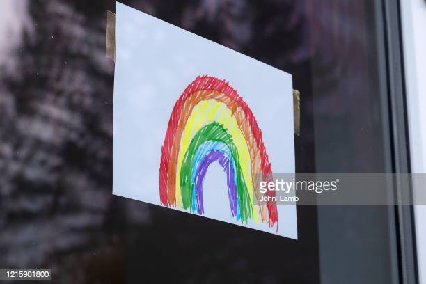 child's rainbow picture displayed in a window as a symbol of hope during covid-19 lockdown.. - window stock pictures, royalty-free photos & images