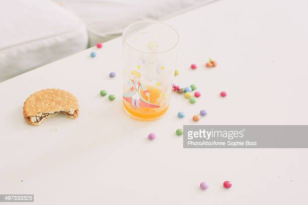 Child's sweets scattered on table by glass of juice