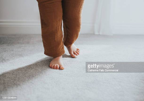 child's taking a step on grey thick pile carpet, casting shadow - temperature stock pictures, royalty-free photos & images