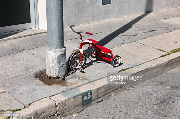 Child's tricycle locked to lamp post in venice beach