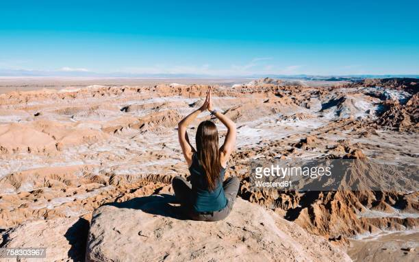 Chile, Atacama Desert, back view of woman practising yoga on a rock