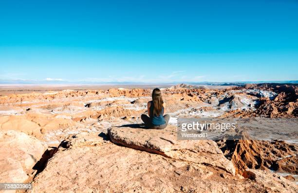 Chile, Atacama Desert, back view of woman sitting on a rock looking at view