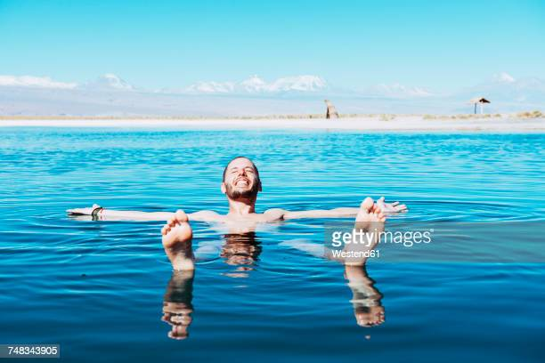 Chile, Atacama Desert, happy man floating in Laguna Cejar