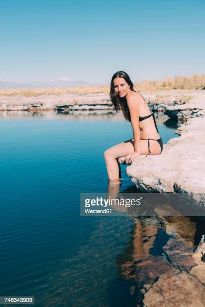 Chile, Atacama Desert, portrait of woman sitting on edge of Laguna Cejar
