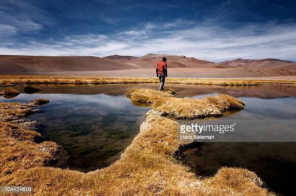 Chile, Atacama, Man walking close to small lagoon