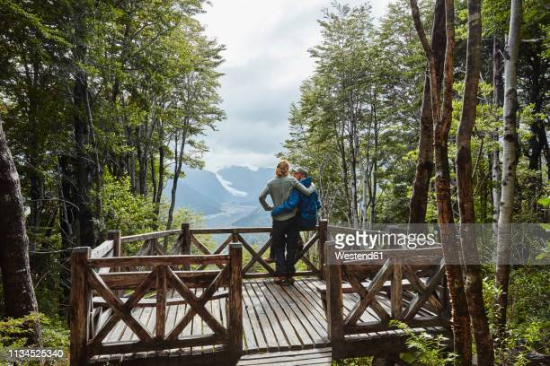 chile, chaiten, parque pumalin, couple on observation deck looking at glacier - observation point stock pictures, royalty-free photos & images