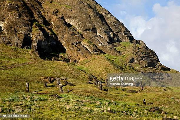 chile, easter island, tourist at rano raraku watching moai statue - rano raraku stock pictures, royalty-free photos & images