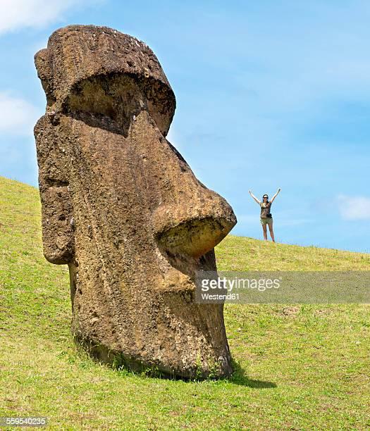 Chile, Easter Island, woman with Moai in Ranu Raraku quarry, in the Rapa Nui National Park