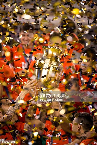 Chile forward Mark Gonzalez and Chile forward Mauricio Pinilla lift up the Copa America Championship Cup with confetti falling all around them and...