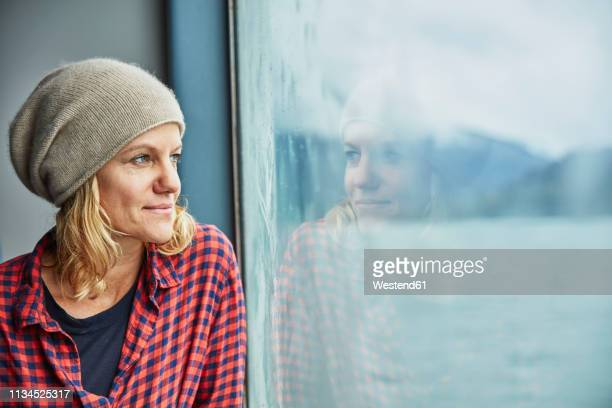chile, hornopiren, portrait of woman looking out of window of a ferry - passagier wasserfahrzeug stock-fotos und bilder