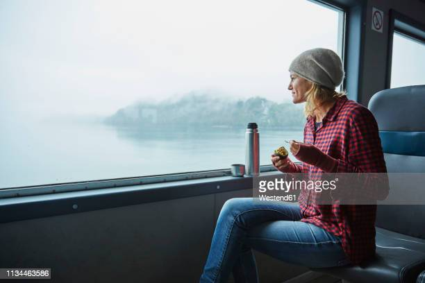 chile, hornopiren, woman looking out of window of a ferry eating an avocado - passagier wasserfahrzeug stock-fotos und bilder