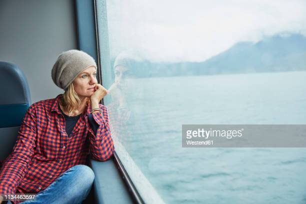 chile, hornopiren, woman looking out of window of a ferry - passagier wasserfahrzeug stock-fotos und bilder