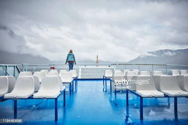 chile, hornopiren, woman standing at rail of a ferry looking at fjord - 船のデッキ ストックフォトと画像