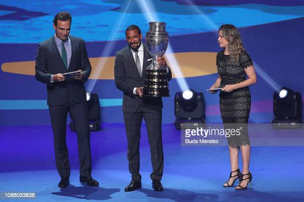 Chile National Football team Player Jean Beausejour presents the Copa America Trophy with Presenters Tadeu Schmidt and Fernanda Gentil during the...