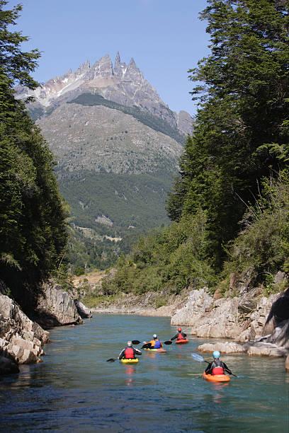 Chile, near Futaleufu, Rio Azul, four men kayaking, rear view
