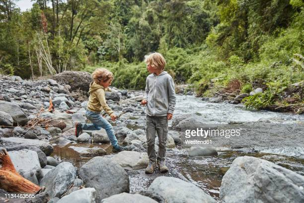 chile, patagonia, osorno volcano, las cascadas waterfall, two boys playing at a river - children only stock pictures, royalty-free photos & images