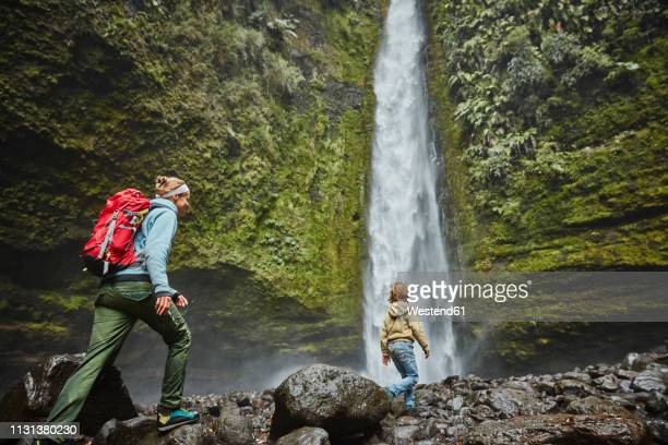 Chile, Patagonia, Osorno Volcano, mother and son walking at Las Cascadas waterfall
