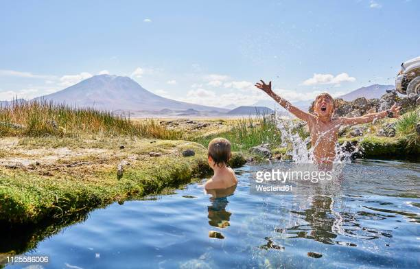 chile, salar del carmen, two boys bathing in hot spring - hot spring stock pictures, royalty-free photos & images