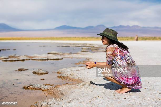Chile, San Pedro de Atacama, woman crouching in the desert at lakeside