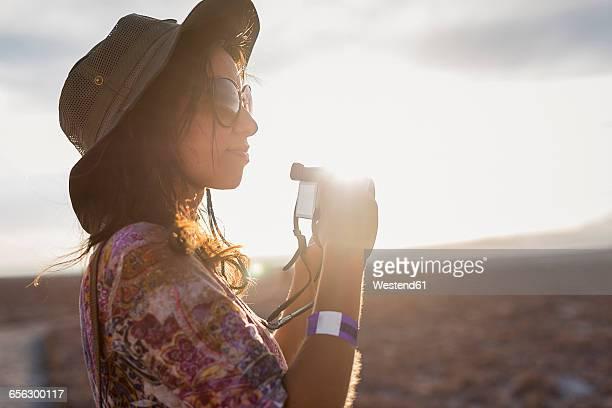 Chile, San Pedro de Atacama, woman with camera in the desert in backlight