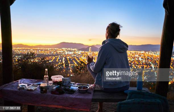 chile, santiago, woman drinking a beer in the mountains above the city at sunset - santiago chile stock pictures, royalty-free photos & images
